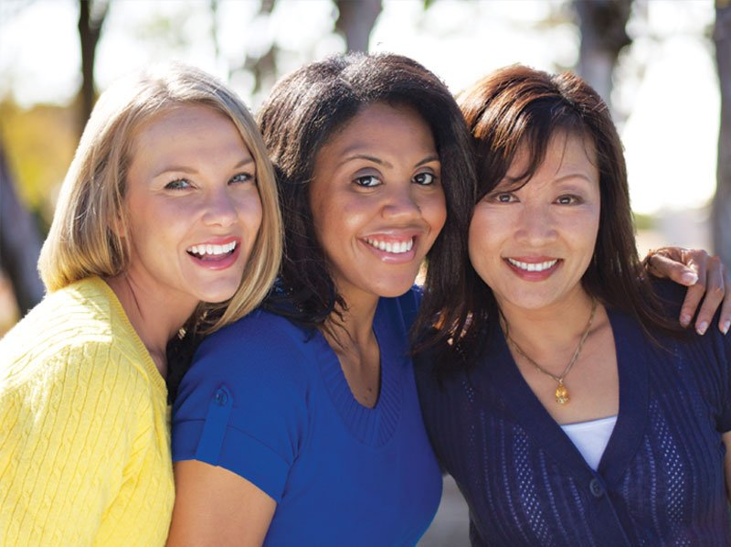 Three women leaning into each other all are smiling