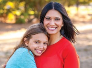 Woman being hugged by young girl in outdoor setting both are smiling